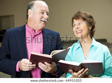 Husband and wife in church, singing hymns. - stock photo