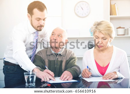 Husband and wife preparing agreement papers in bank with clerk