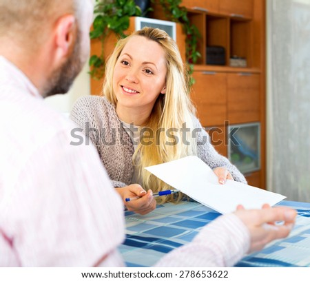 Husband and wife reading insurance contract and smiling - stock photo