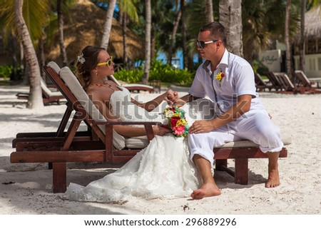 husband and wife relaxing on sunbeds at the beach. - stock photo