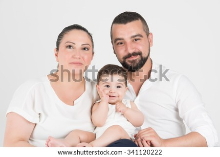 Husband and wife sitting and posing with their cheerful child - stock photo