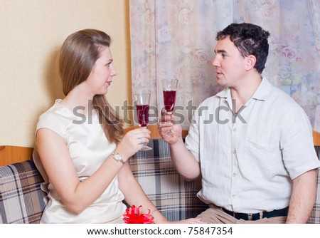 Husband and wife with glasses of wine in the kitchen - stock photo