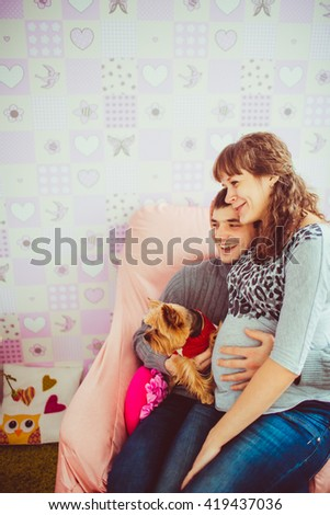 Husband cuddles a pregnant wife and holds a dog - stock photo