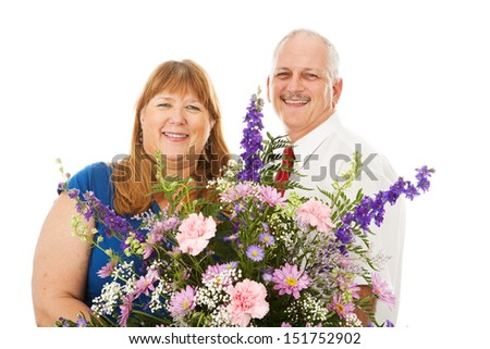 Husband giving his wife a huge bouquet of flowers.  Isolated on white.   - stock photo