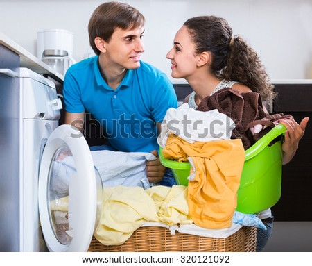 Husband helping happy american housewife to use washing machine indoors - stock photo