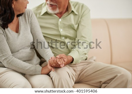 Husband holding hand of his wife when talking to her - stock photo