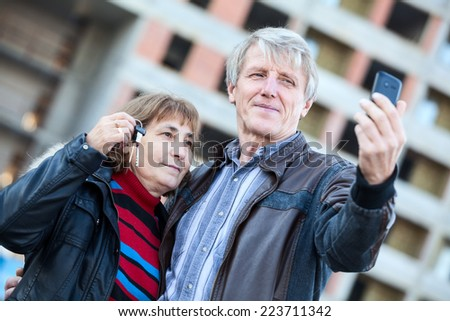 Husband making selfie by phone when wife holding house keys in hand - stock photo