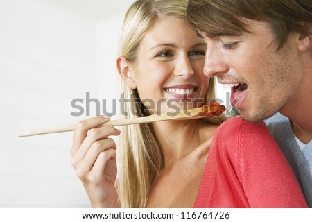 Husband reaching over his wife's shoulder to taste the sauce which she is offering him on the end of the wooden spoon