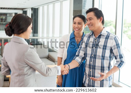 Husband shaking hands with the real estate agent - stock photo