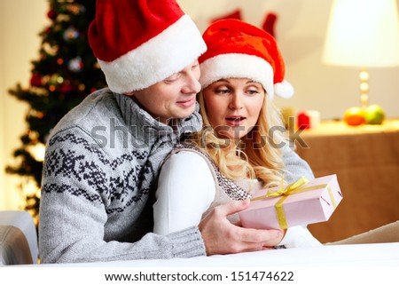 Husband surprising his beloved wife with a Christmas present - stock photo