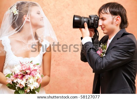 Husband taking picture of his wife on wedding. - stock photo