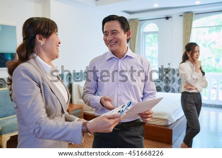 Husband talking to estate broker while wife examining room