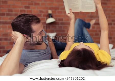 Husband watching his wife read a book with a complacent smile as she lies on her back on the bed alongside him holding the book in the air - stock photo