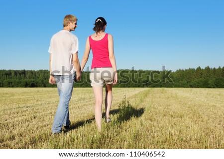 Husband, wife holding hands walking in beautiful field, back - stock photo