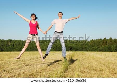 Husband, wife in jump in field - stock photo