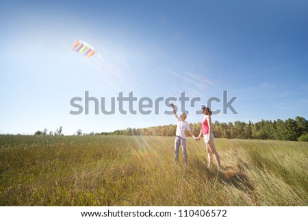 Husband, wife launch kite in field - stock photo