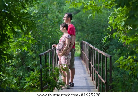 Husband with his pregnant wife on the bridge in green forest - stock photo
