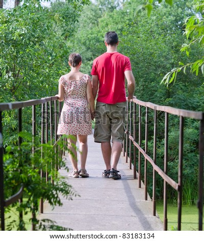 Husband with his wife on the bridge in green forest - stock photo
