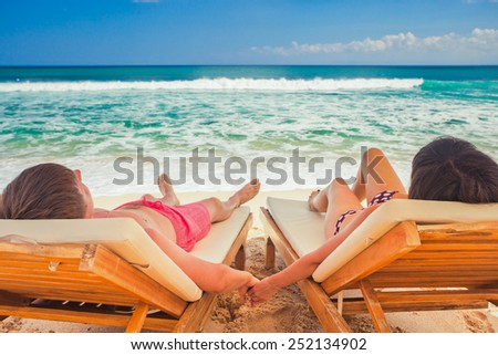 husband with his wife resting near blue ocean, couple just married on beach - stock photo