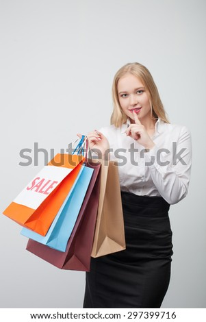 Hush-hush. Beautiful young girl has bought many things and is smiling wilily. She is asking to safe her secret and raising her finger to her mouth. Isolated on background - stock photo