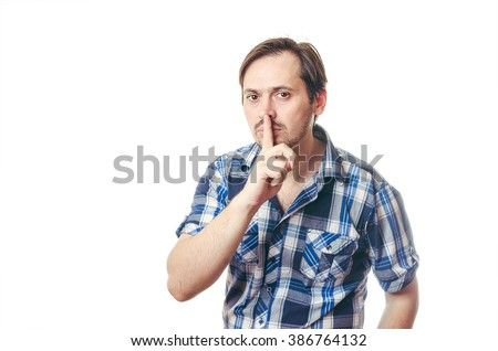 Hush-hush. Pleasant adult man holding his finger in front of the mouth and looking straight while keeping silence. - stock photo