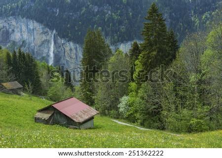 Hut and waterfall in Lauterbrunnen, Switzerland.  - stock photo