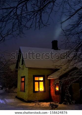 hut in village winter evening scene - stock photo