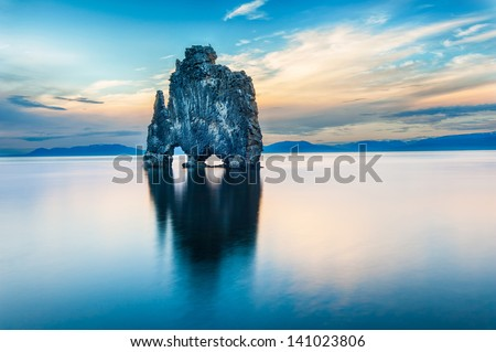 Hvitserkur is a spectacular rock in the sea on the Northern coast of Iceland. Legends say it is a petrified troll. On this photo Hvitserkur reflects in the sea water after the midnight sunset. - stock photo