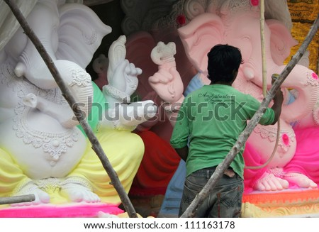 HYDERABAD,AP,INDIA- AUGUST 25:Artists making the ganesha idol for the hindu festival ganesha chathurthi on August 25,2012 in Hyderabad,India.Thousands of Idols in different sizes are made every year.