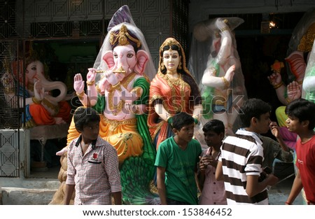 HYDERABAD,AP,INDIA- SEPTEMBER 1:Children looking at Ganesha idols kept for sale during hindu festival ganesh chathurthi on September 01,2013 in Hyderabad,India.Thousands of idols are made every year. - stock photo