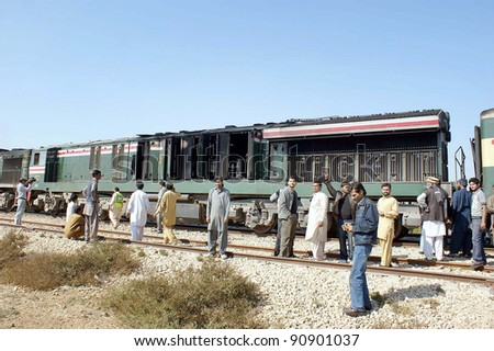 HYDERABAD, PAKISTAN - DEC 15: Karakorum express passengers gather near burnt train engine which caught fire on mainline at Detha station on Thursday, December 15, 2011 in Hyderabad, Pakistan.