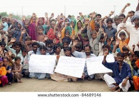 HYDERABAD, PAKISTAN - SEPT. 14: Rain affected people from Badin chant slogans in favor of their demands during protest demonstration at Hala Naka area in Hyderabad, Pakistan on  September 14, 2011. - stock photo