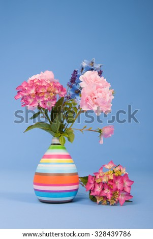 Hydrangeas pink and blue and other flowers on colorful background - stock photo