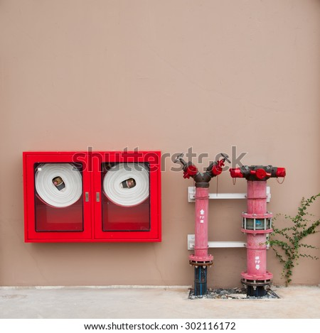 Hydrant with water hoses and fire extinguish equipment on the wa - stock photo