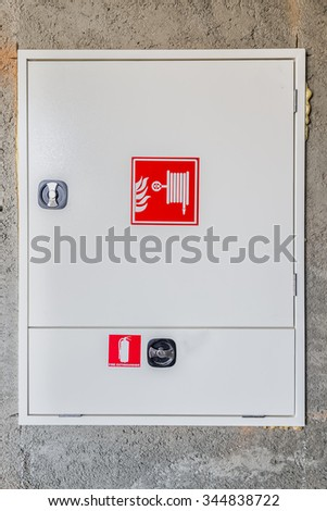 Hydrant with water hoses and fire extinguisher equipment.Fire Extinguisher Cabinets. - stock photo