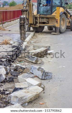 hydraulic arm breaking, installed on the arm of an excavator on building site - stock photo