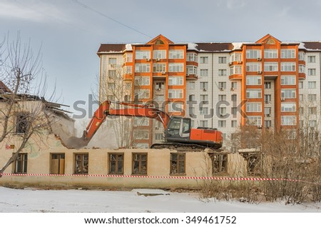 Hydraulic crusher excavator backoe machinery working on site demolition - stock photo
