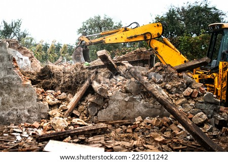 Hydraulic crusher, industrial excavator machinery working on a rainy site demolition  - stock photo