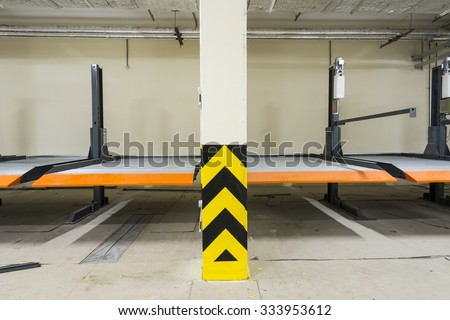 Hydraulic lift for the car in the underground parking. - stock photo