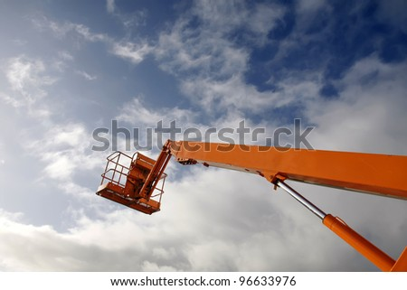 Hydraulic lift machine against a blue sky - stock photo