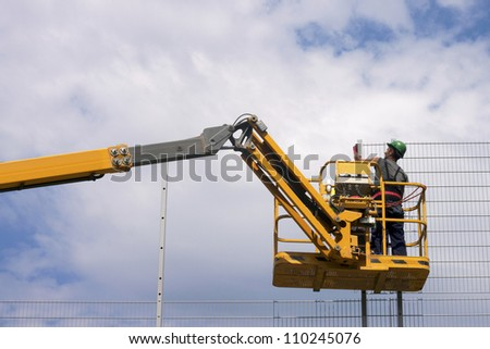 Hydraulic mobile construction platform elevated towards a blue sky with construction workers - stock photo