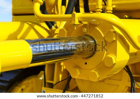 Hydraulic piston system for bulldozers, tractors, excavators, chrome plated cylinder shaft of yellow machine, construction heavy industry detail, selective focus  - stock photo