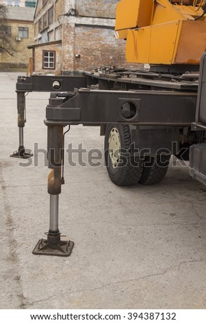 Hydraulic stops on the crane. Hydraulic legs on crane trucks. - stock photo