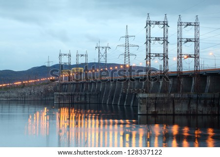 Hydroelectric power station on river at evening, posts with high-voltage wires. - stock photo