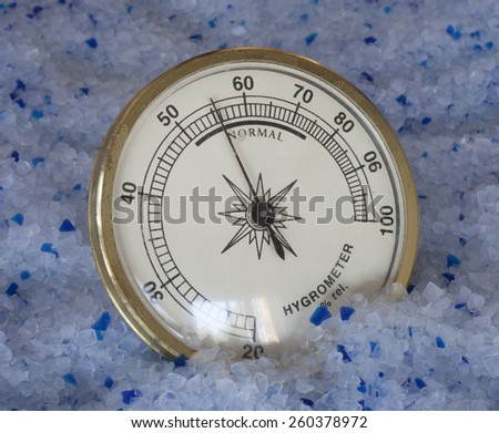 Hygrometer with a high humidity reading on silica kitty litter - stock photo