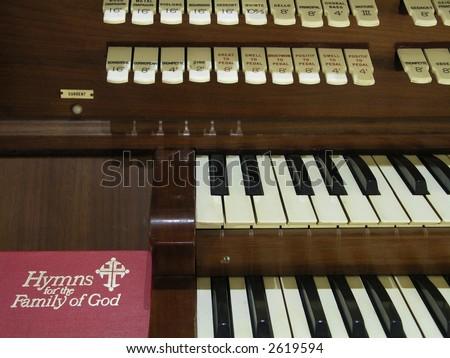 Hymnal resting beside a church organ. - stock photo