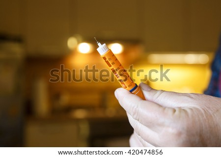 Hyperglycemic diabetic patient with prepared insulin shot at home in the kitchen before eating. Medical process, self-diagnose, common metabolic, widespread and modern epidemic disease concept.   