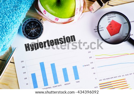 "Hypertension"" black text on paper with magnifying glass on red spider bar on wooden table with compass, pen, towel, green apple with measurement tape, and whistles - fitness, diet and healthy concept - stock photo"