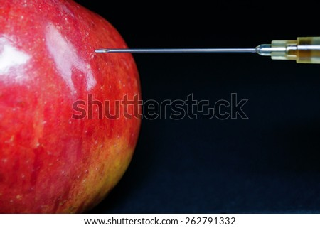 Hypodermic Needle injects a red apple with a brown liquid - stock photo
