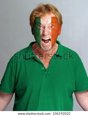 Hysterical supporter with the Irish flag painted on his face - stock photo